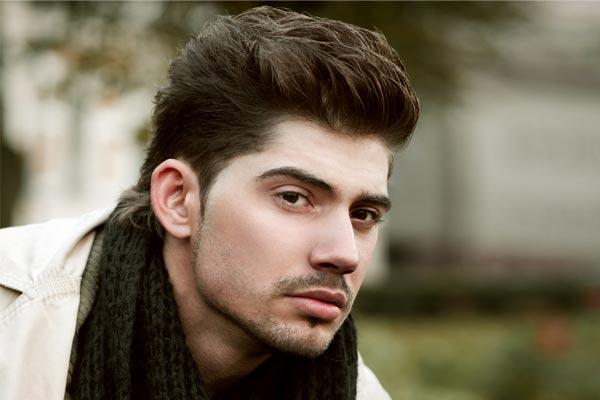 fryzura dla pana młodego z gęstych włosów z nastroszoną górą i zaczesanymi bokami