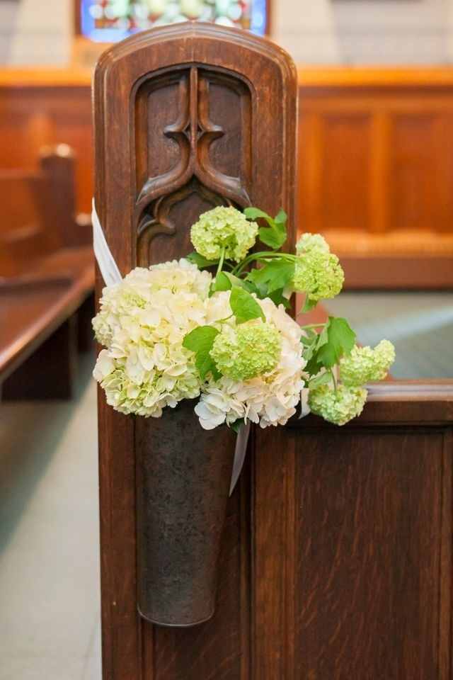 ślubne dekoracje z kwiatów na ławkach w kościele